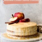 Bourbon Apple Cider Cake topped with apples and cinnimon sticks on a marble platter