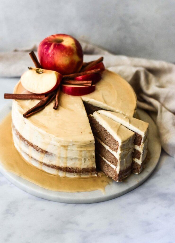 Bourbon apple cider donut cake with a honey glaze on a marble plate.