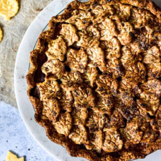 Cheddar apple pie with leave crust decoration on a marble plate.