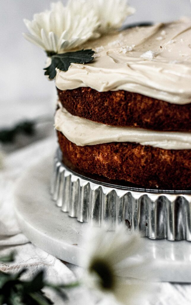 close up of the layers of banana cake with bourbon caramel frosting on a cake stand.