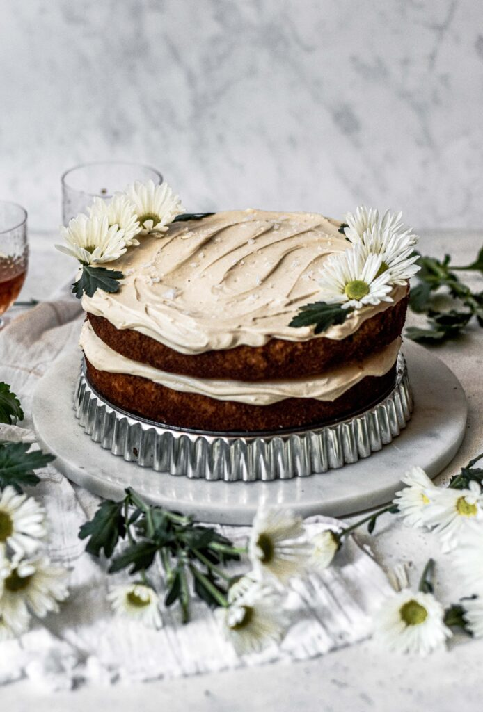 Bourbon Banana Cake decorated with flowered on a cake stand