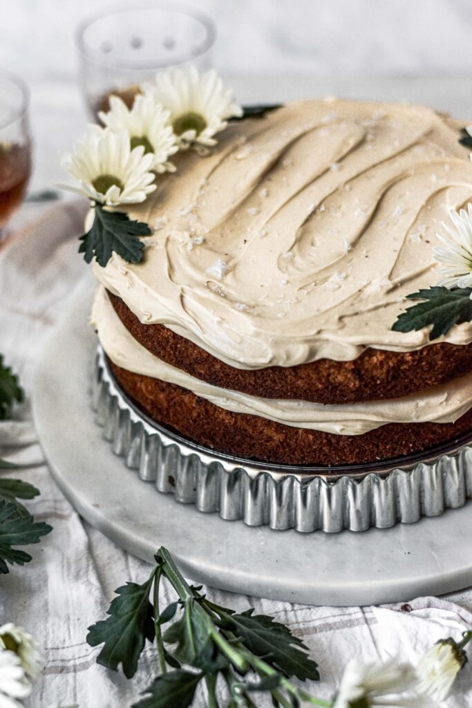 Two layer banana cake with bourbon caramel frosting on a cake stand.