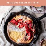 Dutch Baby in a cast iron skillet with fresh strawberries