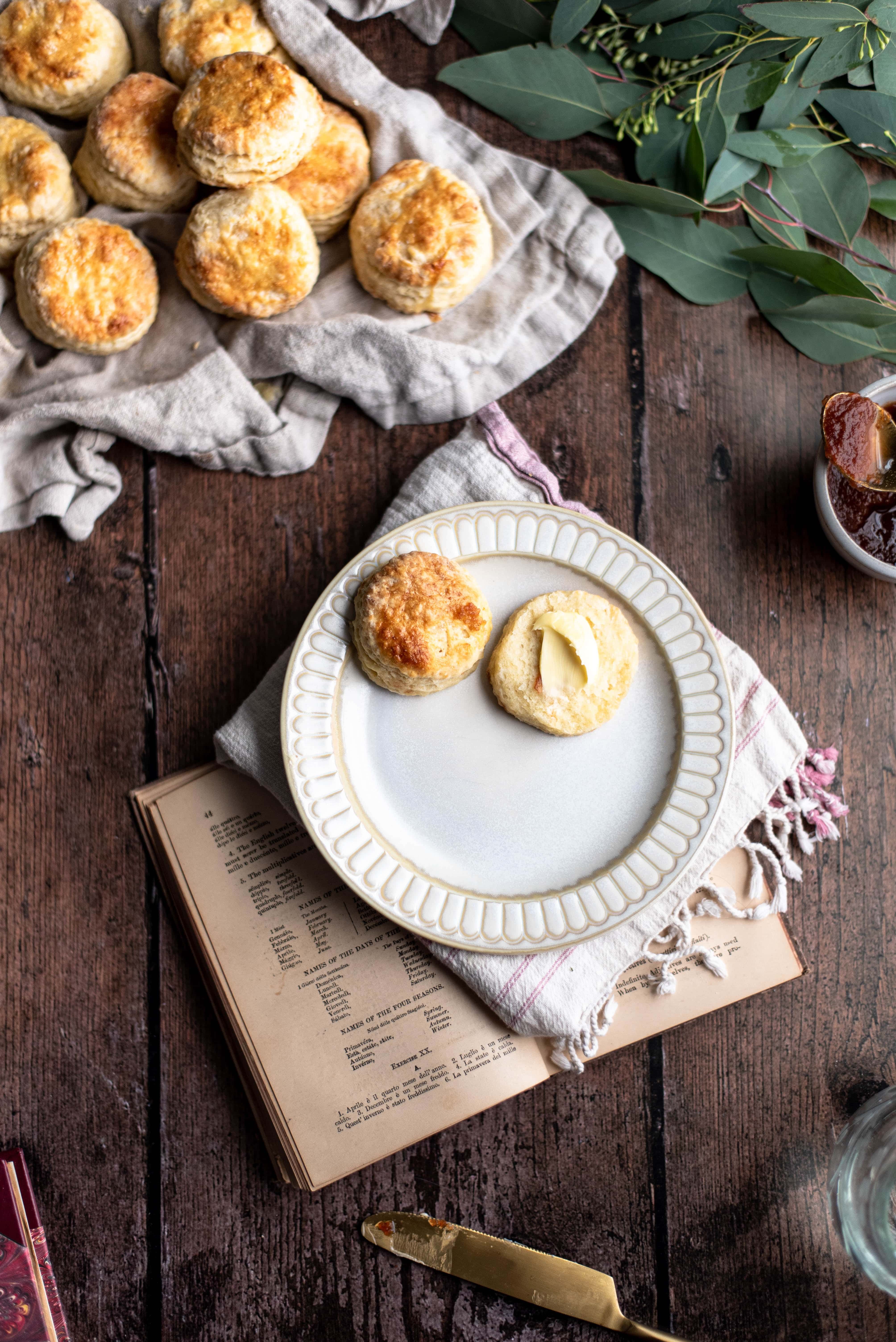 Biscuits on a cream plate with butter smeared in on one on top of a wood table with a old book.