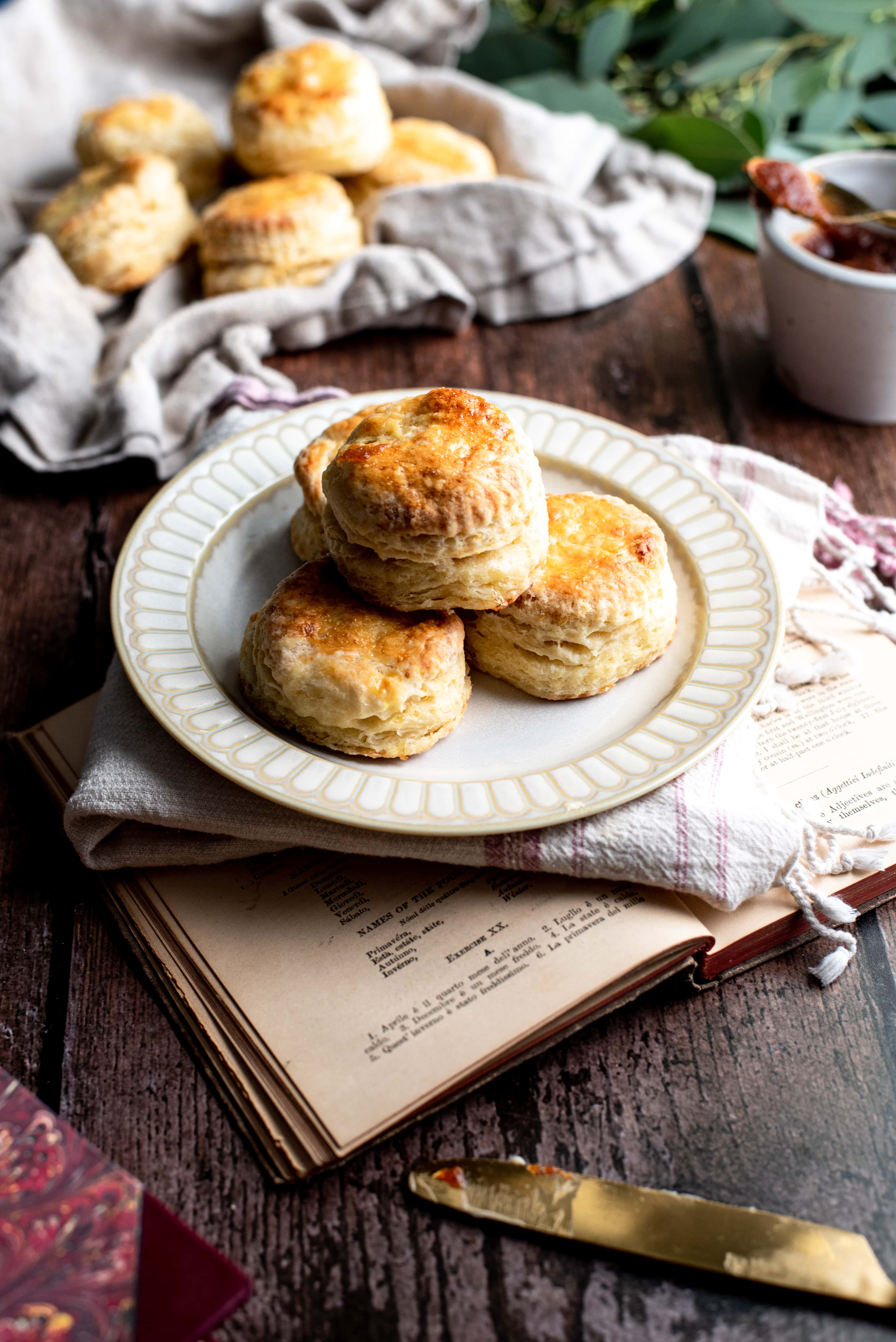Stack of biscuits on a cream plate on top of a wood table with a old book.