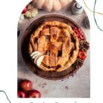 caramel apple pie on a wood cake stand surrounded by apples and pine cones
