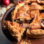 Pie on a wood cake stand with a slice being taken out