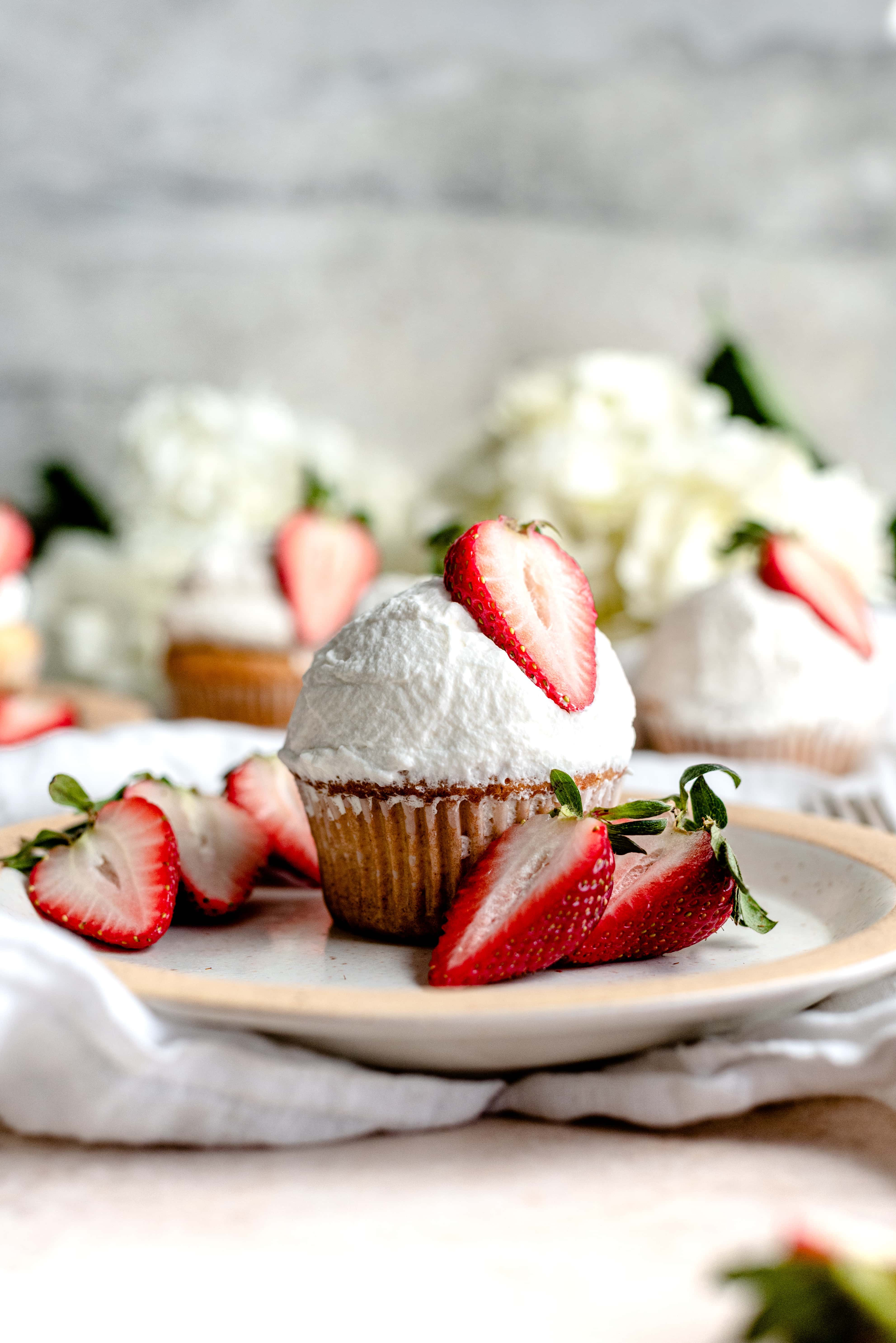 Strawberry Shortcake Cupcake on a plate with fresh strawberries