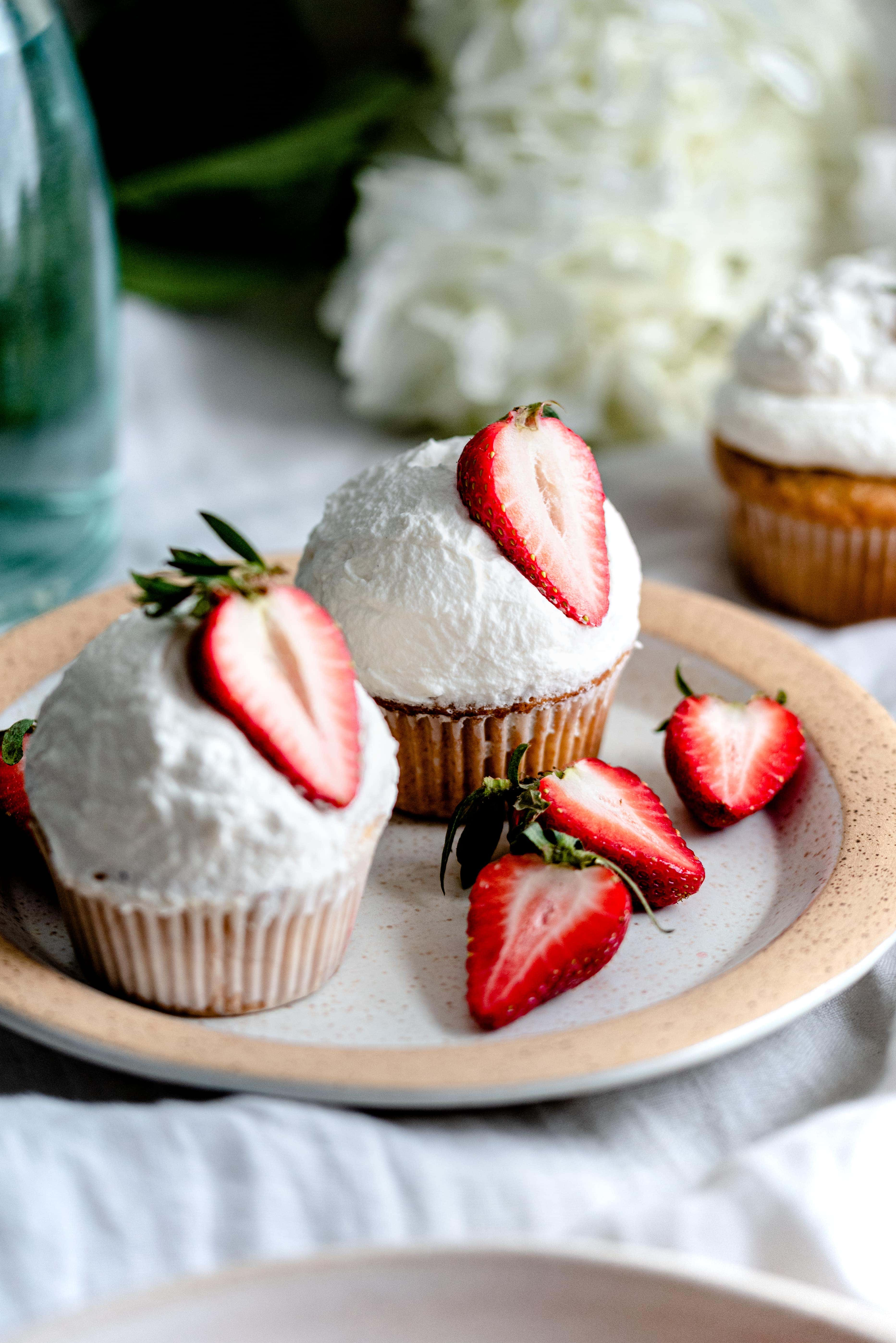 Two strawberry cupcakes topped with whipped cream on a plate