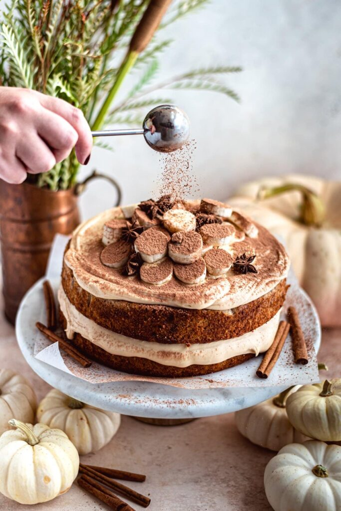 banana layer cake on a marble cake stand being dusted with chocolate.