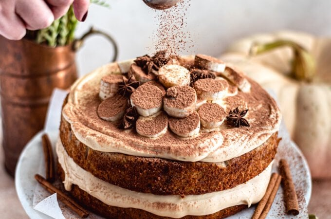 banana layer cake being dusted with chocolate on a marble cake stand.