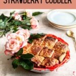 Strawberry cobbler in a pie dish on a table with a gold spoon off to the side