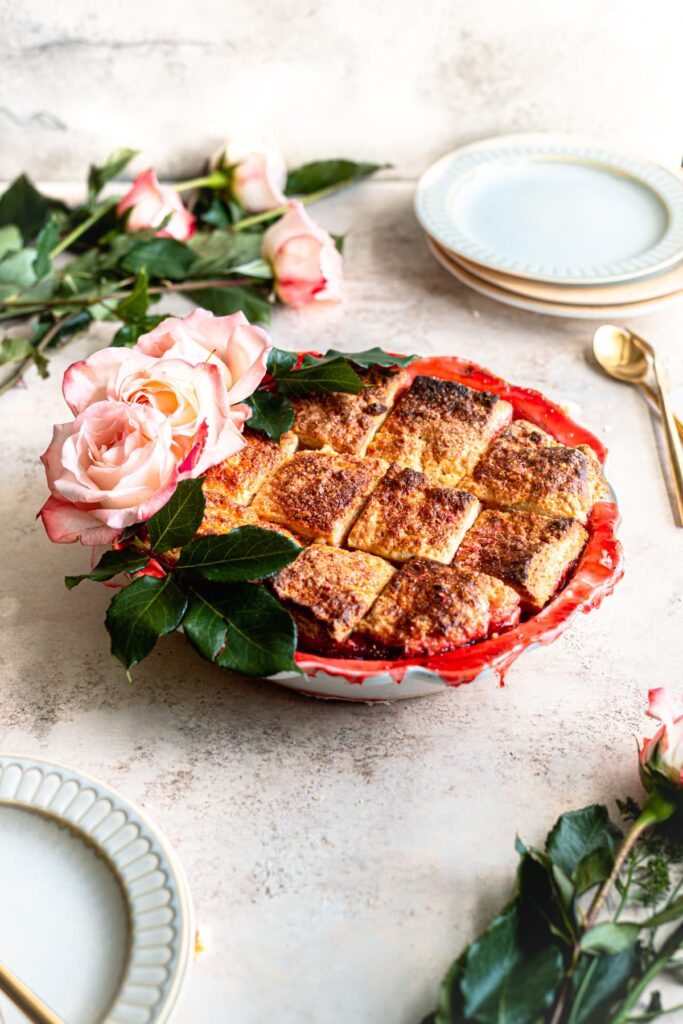 Strawberry cobbler in a pie dish with roses on the left side on a table with empty plates off to the sides