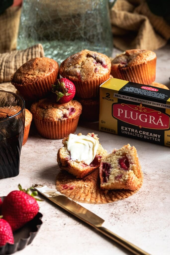strawberry muffin cut in half on a table with butter on one of the sides and a box plugra butter off to the side