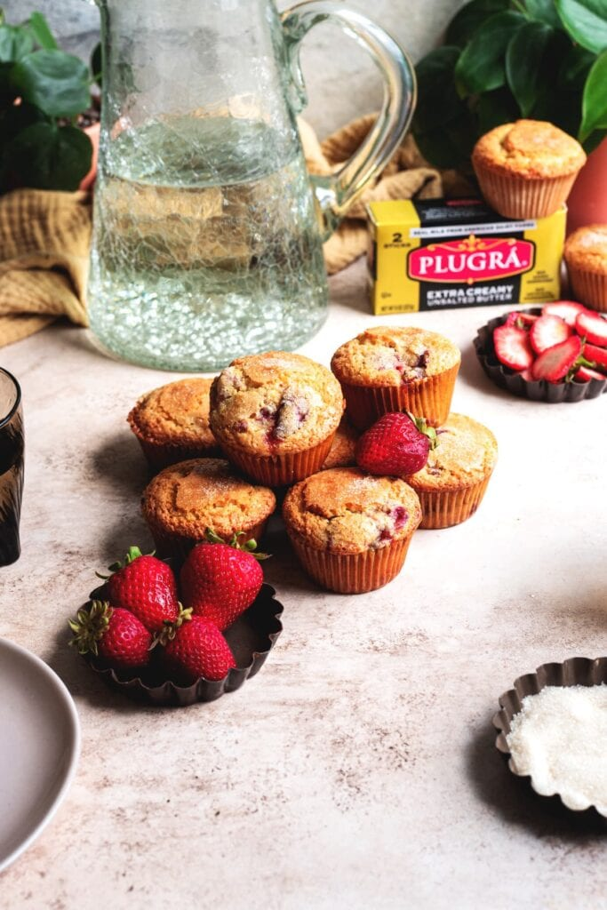 A pile of strawberry muffins on a table with a pitcher of water in the back ground