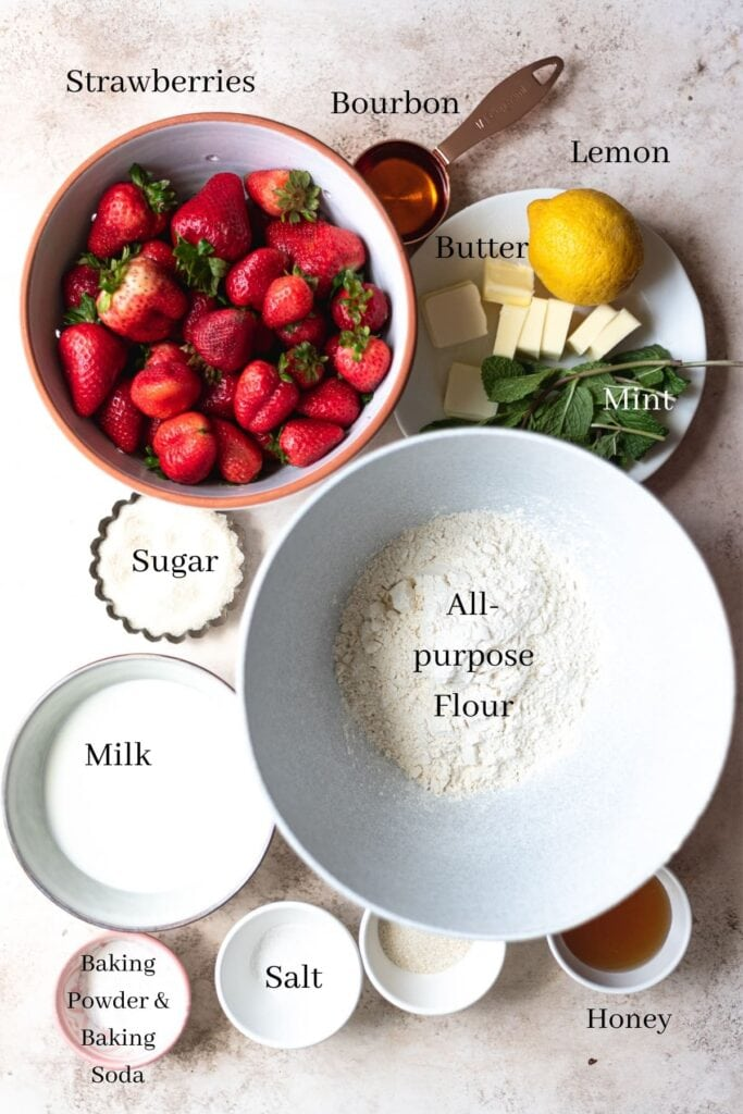Strawberry shortcake ingredients on bowls on a brown table