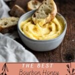 Honey butter in a grey bowl with a piece of bread in the butter