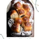 Dinner rolls in a bread basket on a wood table.