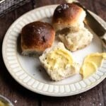 rolls torn in half with butter smeared on them. On a brown plate and on a wooden table.